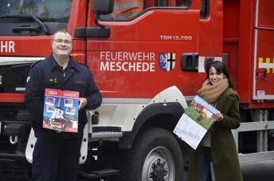 Hans-Jörg Steiner (Freiwillige Feuerwehr der Stadt Meschede) und Steffi Kroggel (Stadtmarketing Meschede) präsentieren den Feuerwehrkalender 2021. Bildnachweis: Stadtmarketing Meschede
