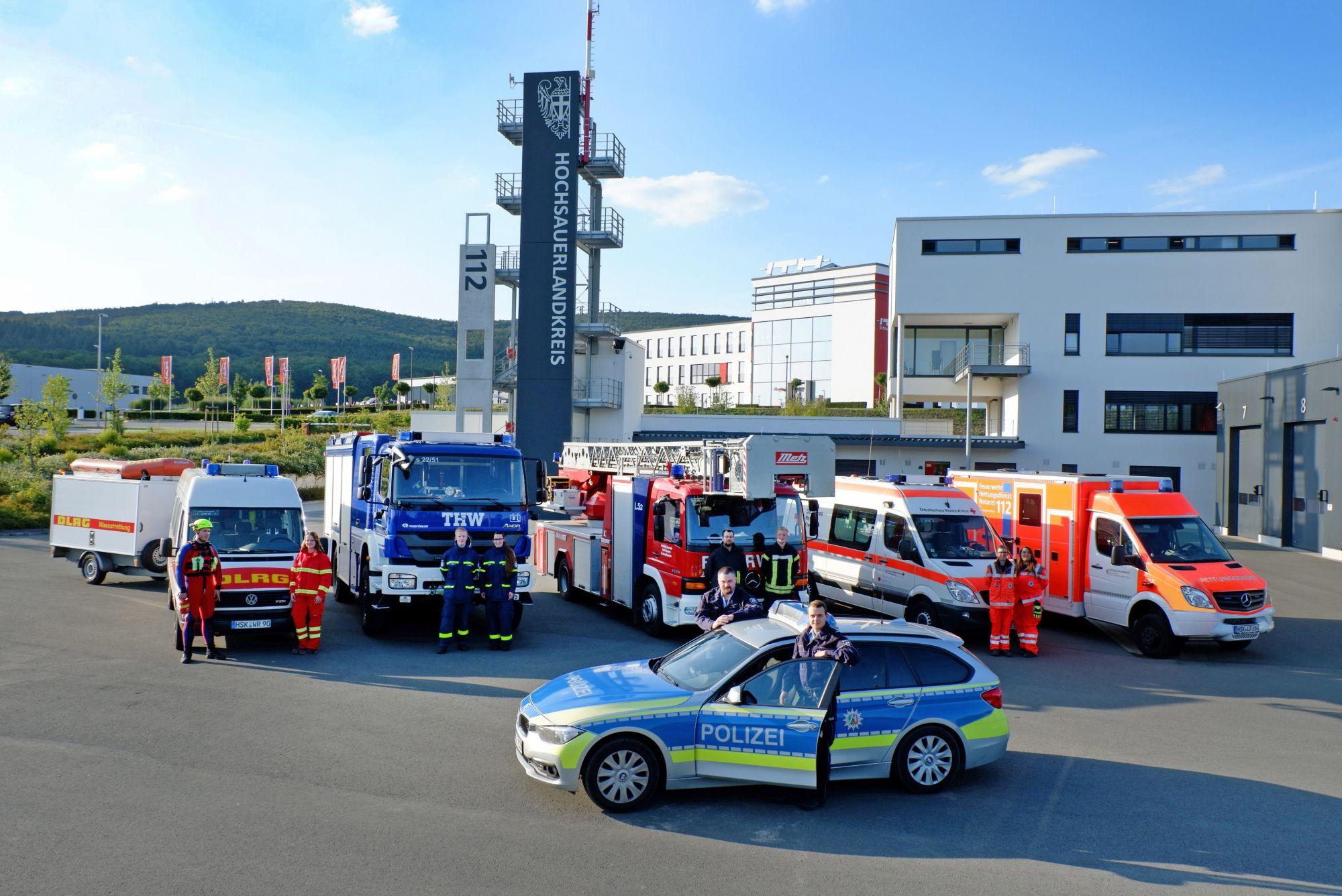 Rettungskräfte vor dem Übungsturm des  Zentrum für Feuerschutz und Rettungswesen in Enste. Auch hier ist die 112 sichtbar angebracht.